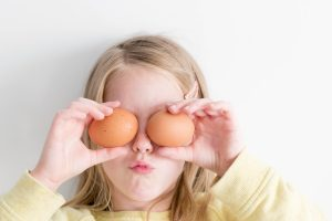 cooking at home with kids | little girl holding two eggs in front of her eyes