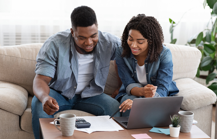 advantages of credit unions | African American couple sitting on the couch happily discussing finances